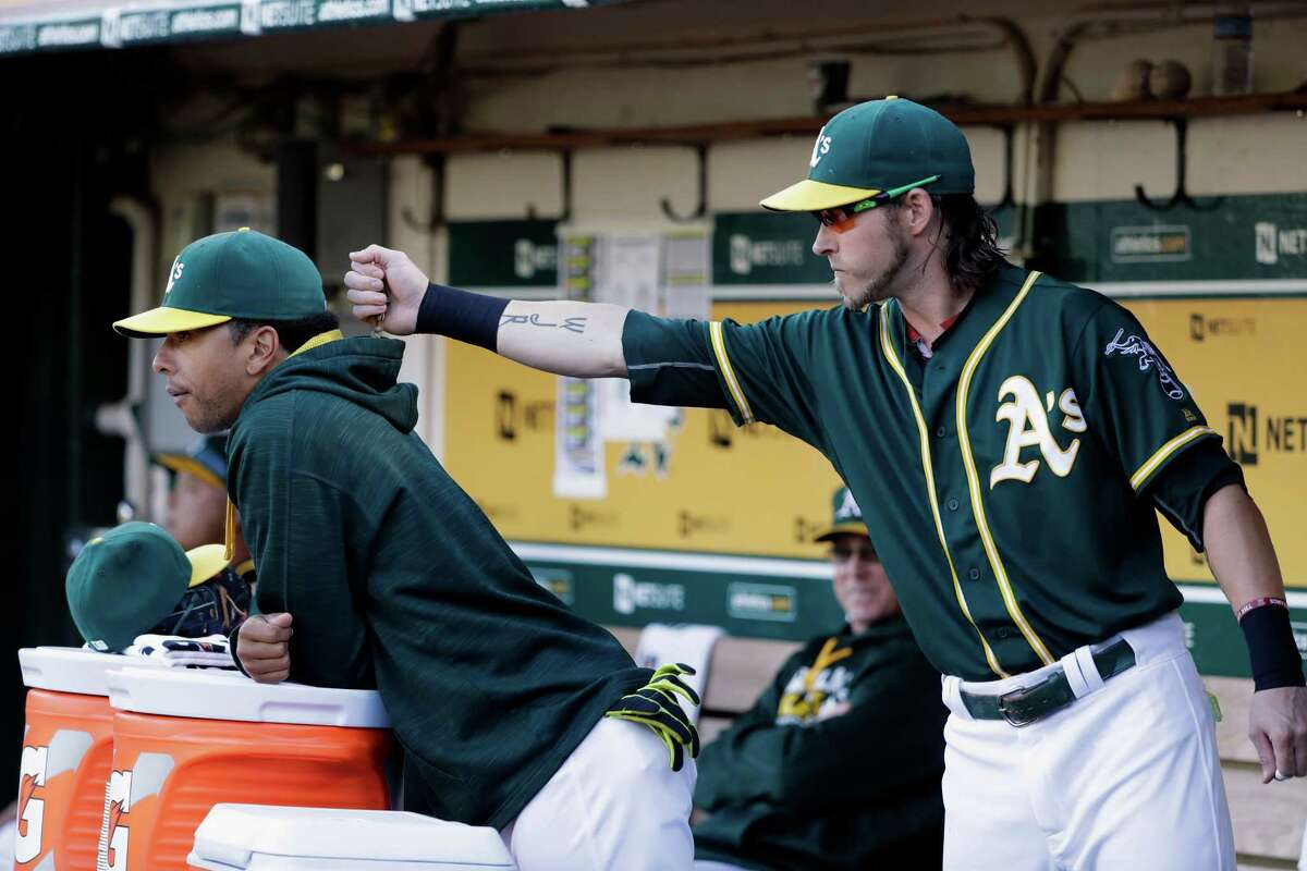 Oakland Athletics' Josh Reddick, right, places sunflower seeds inside the hood of Tyler Ladendorf during the first inning of a baseball game against the Houston Astros Monday, July 18, 2016, in Oakland, Calif. (AP Photo/Marcio Jose Sanchez)