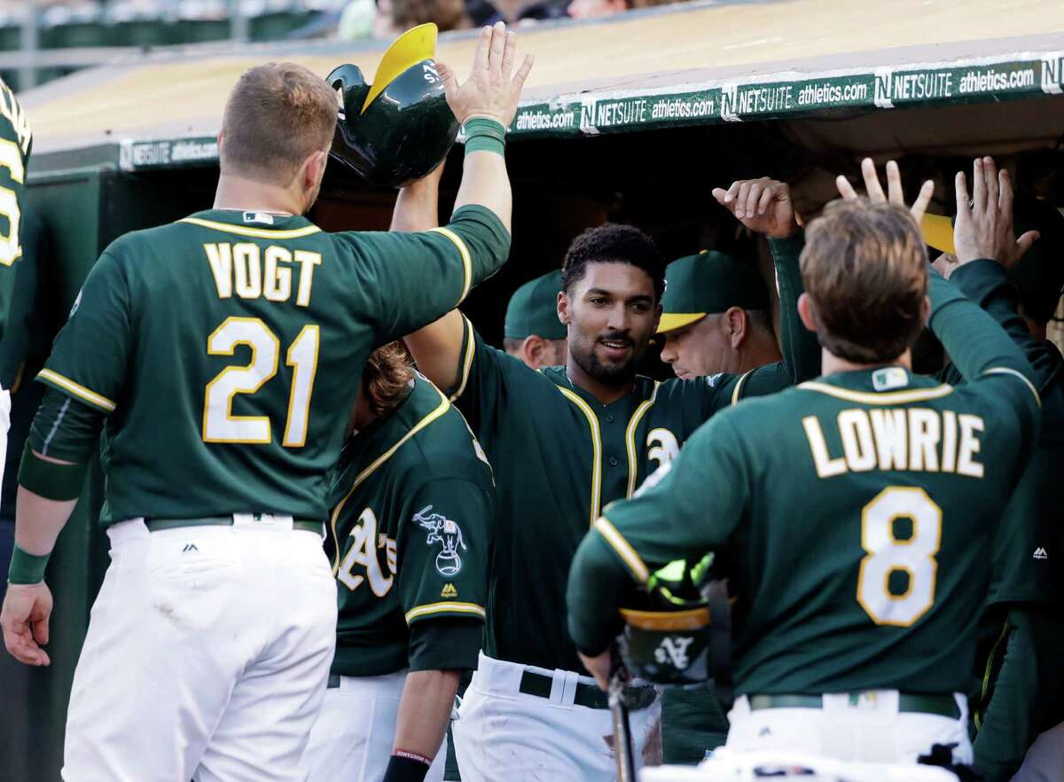 July 18: Athletics 7, Astros 4 Oakland Athletics' Marcus Semien, center, is high-rived in the dugout after scoring on a double from Yonder Alonso during the second inning of a baseball game against the Houston Astros Monday, July 18, 2016, in Oakland, Calif. (AP Photo/Marcio Jose Sanchez)