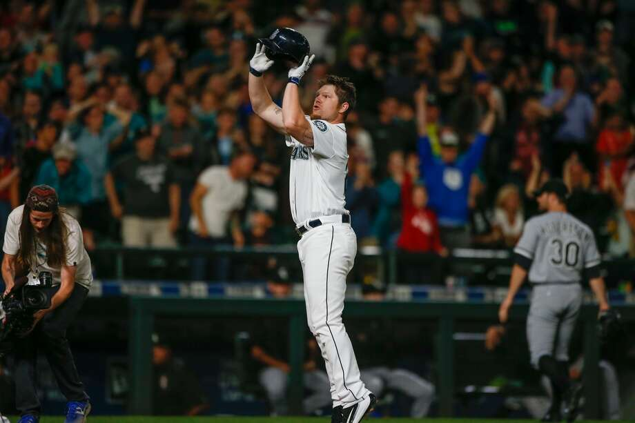 """SEATTLE, WA - JULY 18:  Adam Lind #26 of the Seattle Mariners """"jump shoots"""" his helmet as he crosses home plate following a 3-run walk off home run to beat the Chicago White Sox 4-3 at Safeco Field on July 18, 2016 in Seattle, Washington.  (Photo by Otto Greule Jr/Getty Images) Photo: Otto Greule Jr/Getty Images"""