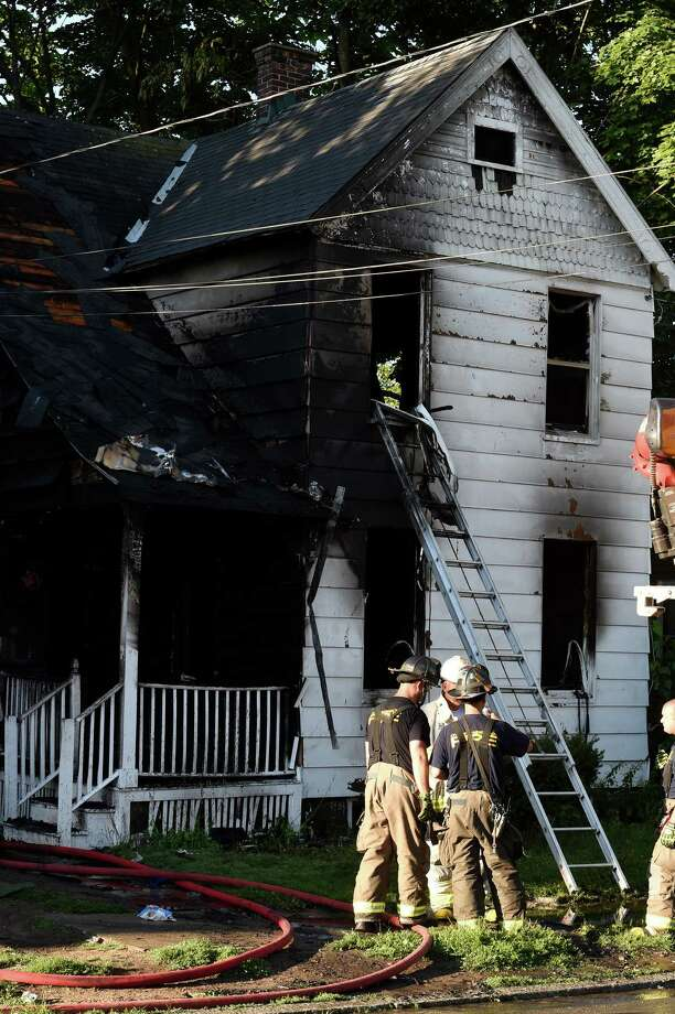 Firefighters wrap up their equipment after a serious fire at 1134 6th Avenue Tuesday  July 19th in Schenectady, N.Y. (Skip Dickstein/Times Union) Photo: SKIP DICKSTEIN