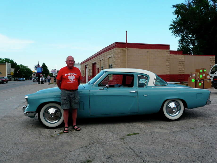John Becker | for the Daily News Dan Derdowski of Auburn stands next to his 1953 Studebaker Coupe at July's 'Movies Under the Moonlight' at TriCity Furniture. This season's free event debuted with a new twist, a car show, that preceded the evening's showing of the movie 'Grease.'