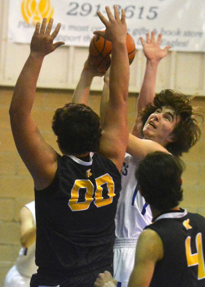Plainview Christian Academy's Ben Shaw goes up for a shot despite tight defense by Kress's Brennon Amador (00) during a game at the PCA gym Tuesday night. The Eagles overcame a four-point deficit with a 31-7 run in the fourth quarter to win by 20 points. Photo: Skip Leon/Plainview Herald