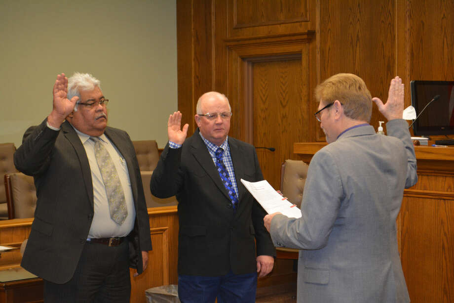 Beginning Sixth TermsDoug McDonough/Plainview HeraldCounty Commissioners Precinct 2 Mario Martinez and Precinct 4 Benny Cantwell receive their oaths of office from County Judge Bill Coleman at a New Year's Day Swearing Ceremony on Thursday. Martinez and Cantwell were both elected to the county commissioners court during the same general election 20 years ago and are now starting their sixth terms in office.