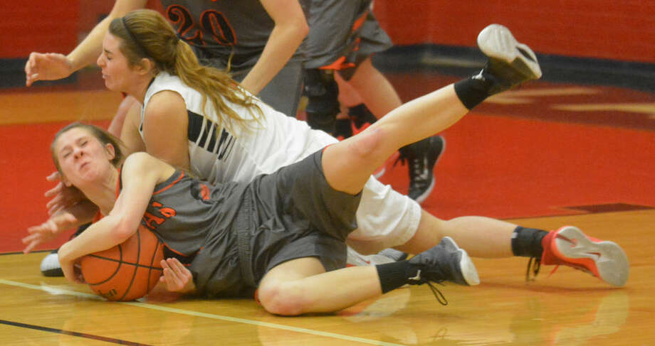 Plainview's Karley Thrasher (white jersey) dives on the floor attempting to grab a loose ball as a Dumas player battles to keep possession. The Lady Bulldogs defeated Dumas, 59-46. Photo: Skip Leon/Plainview Herald