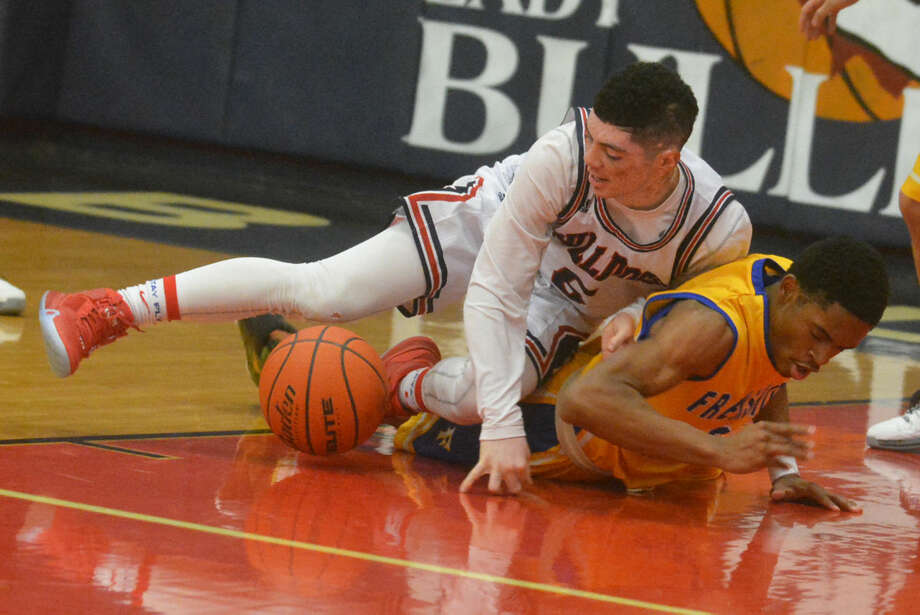 Plainview's Jayton Ellis (top) scrambles on the floor after a loose ball with a Frenship player during a game at the Dog House Tuesday night. Ellis had team-highs of 19 points and eight assists to lead the Bulldogs to victory in their final non-district tuneup. Photo: Skip Leon/Plainview Herald