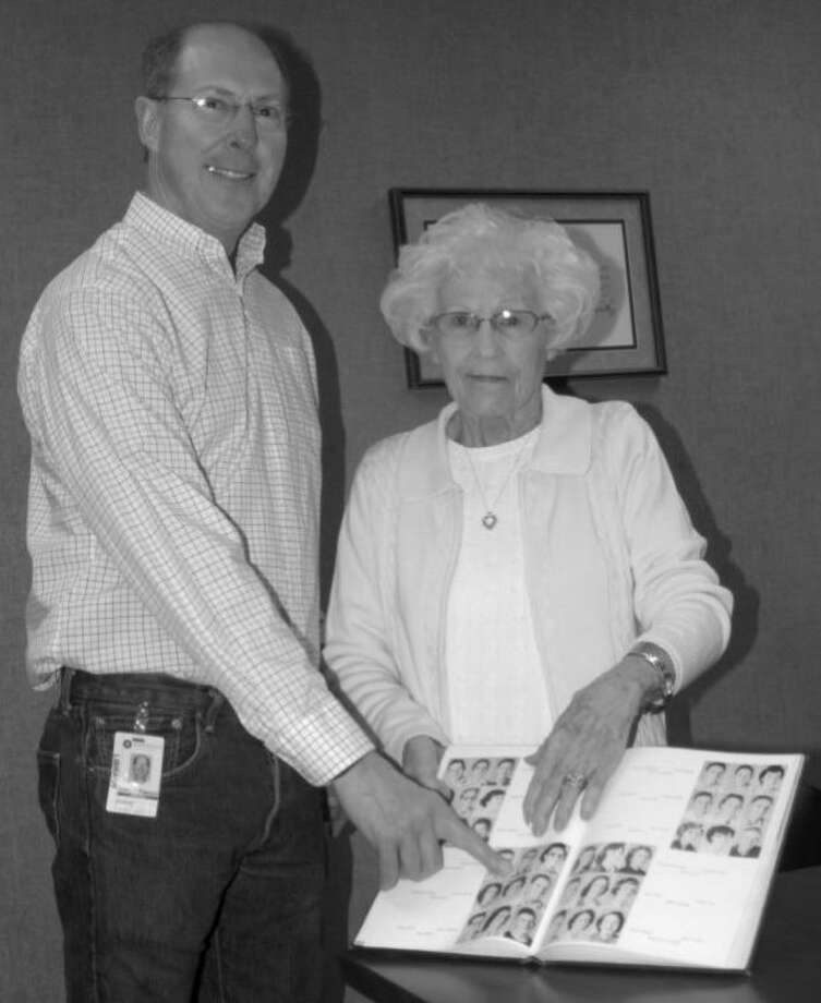 Head Librarian John Sigwald points to a picture of Kenneth Duckett while Cleta Duckett holds the long-sought hardback edition of The Plain View 1953. Photo: Doug McDonough | Plainview Herald