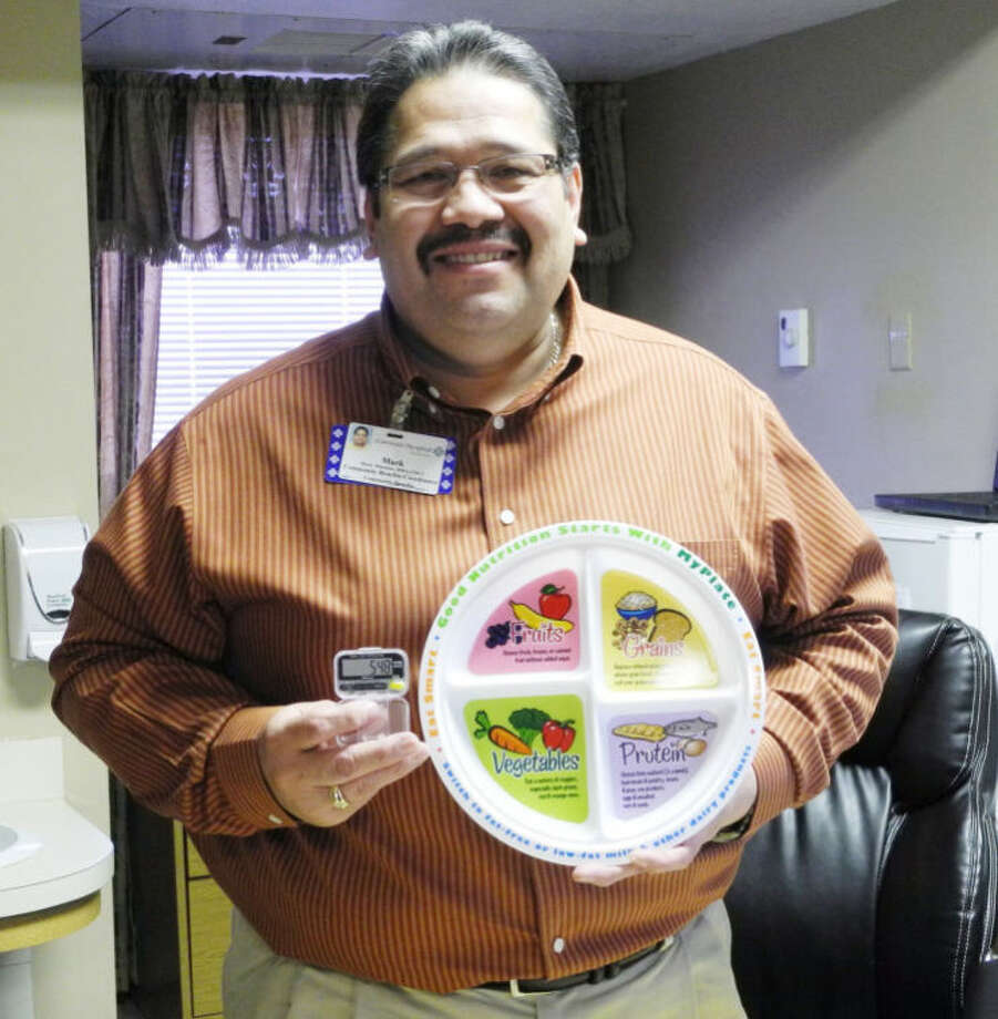 Mark Martinez, Health and Wellness Coordinator at Covenant Hospital Plainview, holds a plate divided into healthy portion sizes and a pedometer. Both are tools used to help people be proactive in staying healthy. Photo: Gail M. Williams | Plainview Herald
