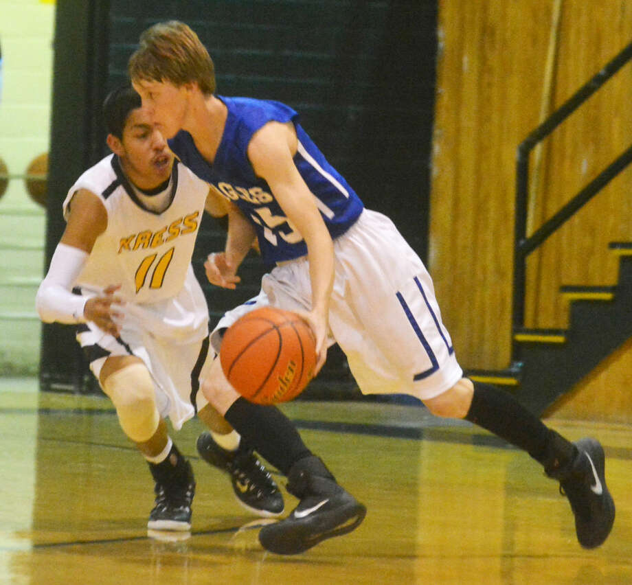 Plainview Christian Academy's Josh Brown dribbles around Kress's Andrew Reyes during a basketball game in Kress Tuesday night. Brown put in an offensive rebound at the buzzer to lift PCA to a 48-47 victory. Reyes had scored with 12 seconds left to give Kress a one-point lead. Photo: Skip Leon/Plainview Herald