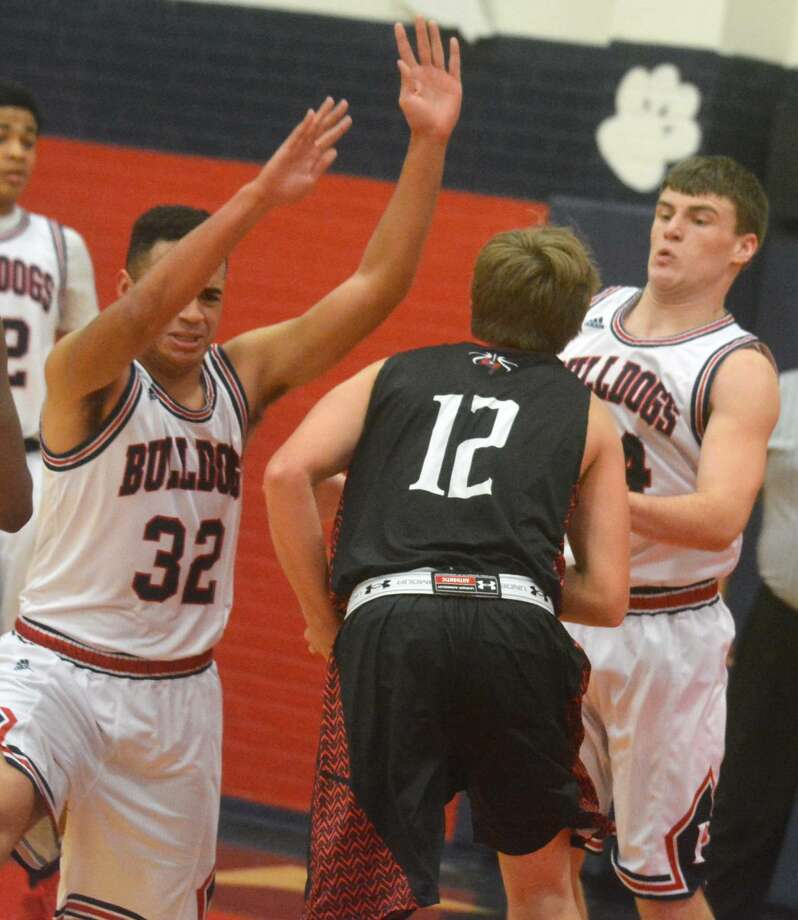 Plainview's Marc Wallace, 32, and Beaux Bennett, right, converge on an opponent in the lane during a game earlier this season. The Bulldogs won at San Angelo Lake View Tuesday night to improve to 2-0 in District 4-5A. Photo: Skip Leon/Plainview Herald