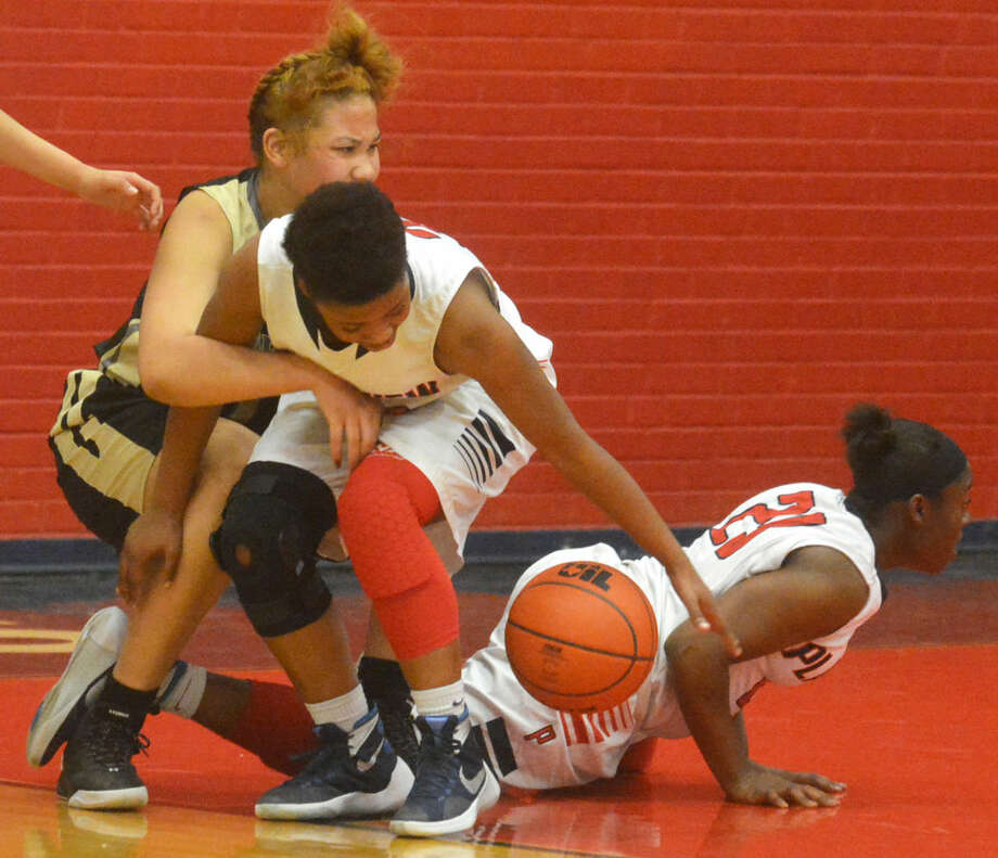 Plainview's Khyra Riddley (center) tries to grab a loose ball as Lubbock's Kymera Terry (left) holds onto her during a game Friday night. Plainview's Jade Nails (23) also goes for the ball. Lubbock handed the Lady Bulldogs their first District 4-5A loss, 60-45. Photo: Skip Leon/Plainview Herald