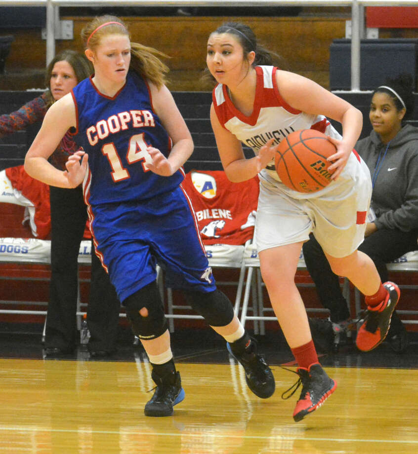 Plainview's Taryn Garza (right) tries to get past an Abilene Cooper defender during a junior varsity girls basketball game at the Dog House Tuesday. The Lady Bulldog jayvees overcame a halftime deficit to defeat Cooper, 66-41, in their opening District 4-5A game. Photo: Skip Leon/Plainview Herald