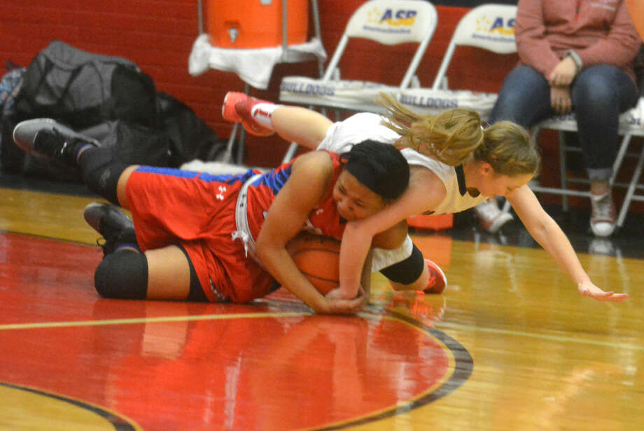 Plainview's Jaden Gonzales, right, dives on the floor and gets a hand on the ball as an Abilene Cooper player cradles the basketball during a District 4-5A game at the Dog House Friday night. Gonzales scored 18 points to help the Lady Bulldogs to a 57-49 win, raising their record to 4-1 in district play. Photo: Skip Leon/Plainview Herald