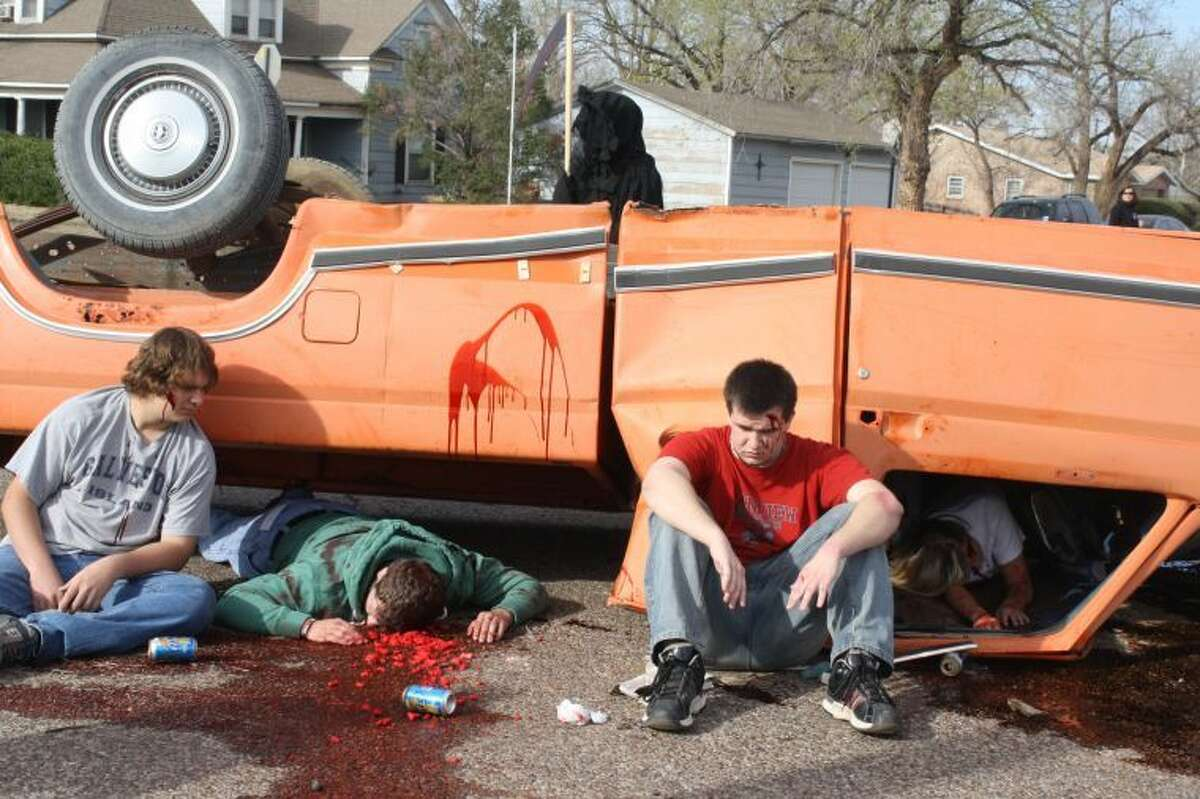 """With the Grim Reaper in the background, PHS students Aaron Thompson (left) Brendan Voss, Taylor McCasland and Shannon Watson portray students in an alcohol-related crash. The scene is part of """"Shattered Dreams,"""" meant to give students an understanding of the realities of drinking and driving."""