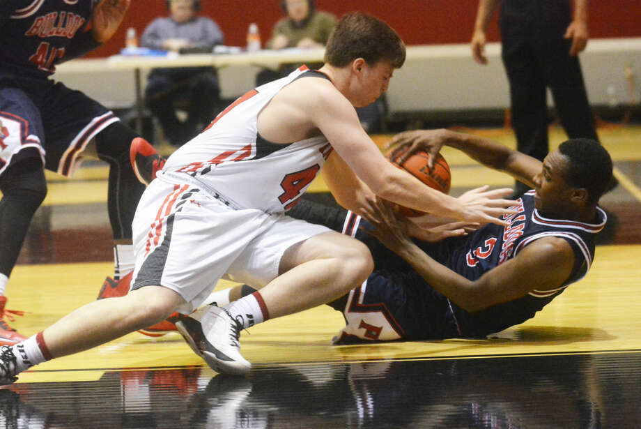Plainview's Ben McGee falls to the floor clutching the basketball as Lubbock Cooper's Garrett Robertson falls on top of him during a District 4-5A basketball game Friday night. Photo: Skip Leon Plainview Herald