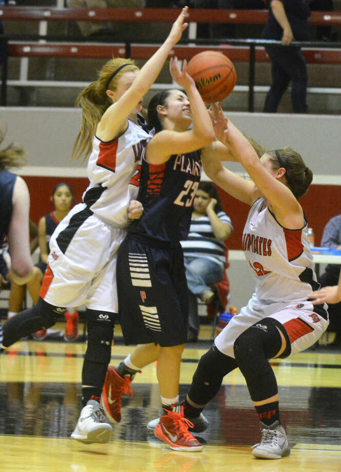 Plainview's Karli Wheeler is sandwiched between two Lubbock Cooper players as she drives to the basket Friday night. The three-time all-state selection has been nominated to play in the McDonald's All-American game April 1 in Chicago. Photo: Skip Leon/Plainview Herald