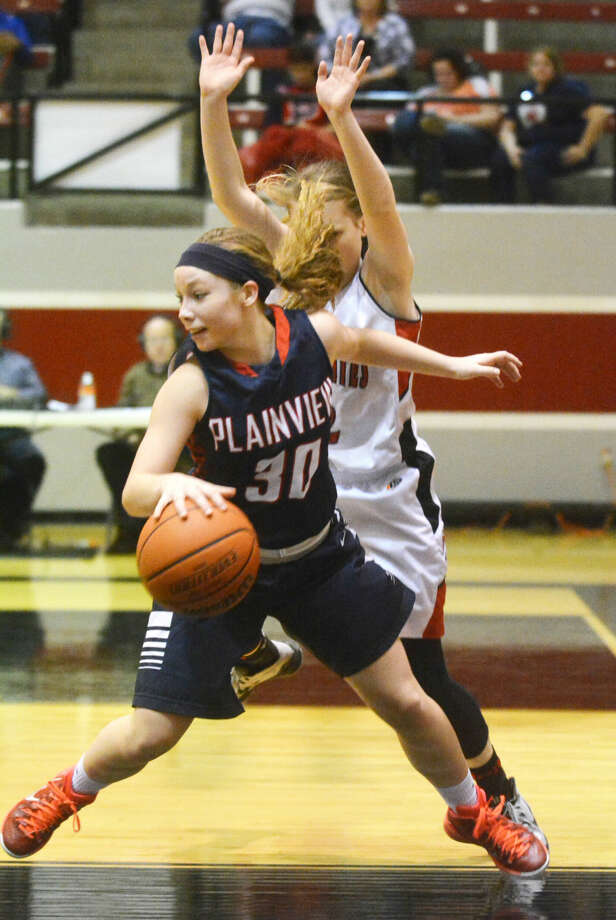 Plainview's Jaden Gonzales dribbles and spins away from a Lubbock Cooper defender during a District 4-5A basketball game in Lubbock Friday. The Lady Bulldogs raised their record to 18-7 overall and 2-0 in district with a victory. Photo: Skip Leon/Plainview Herald