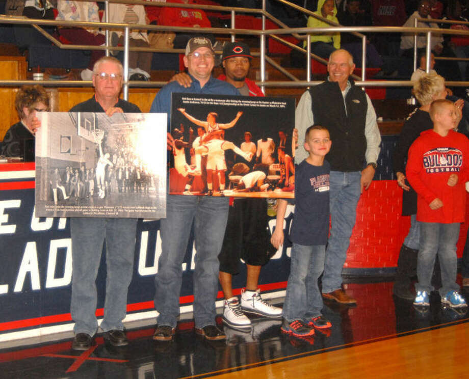 Doug McDonough/Plainview HeraldTwo former Bulldog basketball standouts, Paul Aday (left) and Rob Bass, hold photo enlargements of key moments in Plainview High Bulldog history during special presentation ceremonies between the varsity girls and boys' games against Lubbock High on Tuesday. Aday, who now lives in The Woodlands, displays a photo taken on Feb. 21, 1964, showing him making the winning basket at the buzzer in a 72-71 playoff game between District 3-4A co-champions Plainview and Lubbock High. Bass, of Plainview, holds a photograph taken March 12, 1994. It shows him being held aloft after scoring the winning bucket at the buzzer to lift Plainview over Austin Anderson, 54-52, and win the Class 4A state basketball championship. Both photos will hang in the gym lobby.