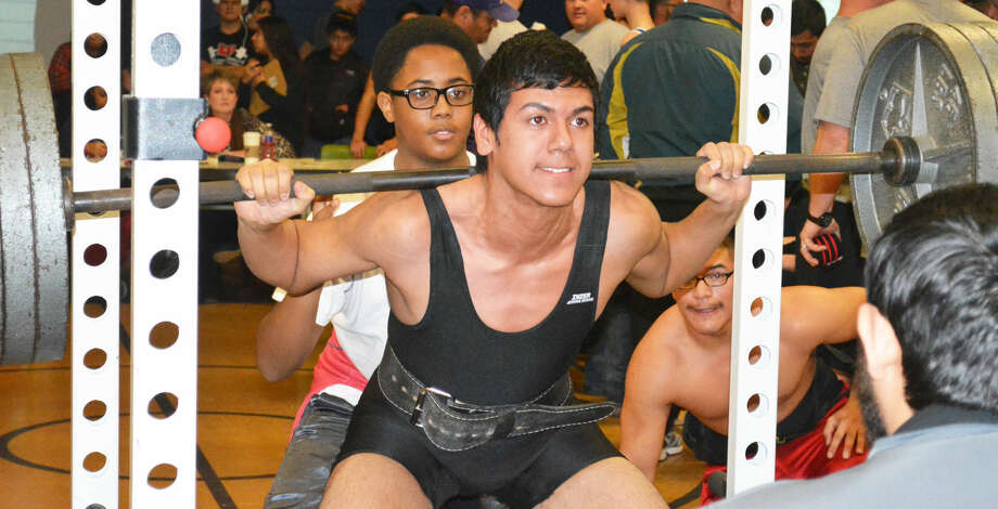 Plainview's Steven Vallejo executes a squat lift as teammate Domingo Saucedo (bottom right) encourages him during the Plainview Invitational Powerlifting Meet Saturday. The Bulldogs won the team championship with 56 points. Photo: Skip Leon/Plainview Herald