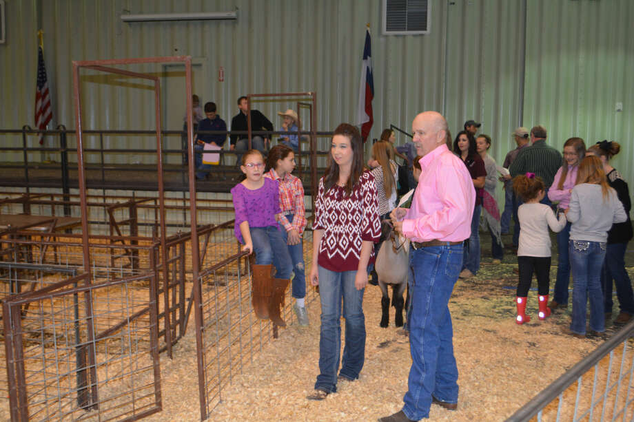 Plainview 4-H Club member Bailey Reese awaits word from show official Mark True before entering the show ring Monday at the premium auction which concluded the 80th annual Hale County Stock Show. While championship animals were brought into the ring for the auction, those with lower placing livestock got to leave their animals in their pens during the bidding. The funds each student receives in the premium auction helps offset the cost of feed and other expenses related to raising show animals.
