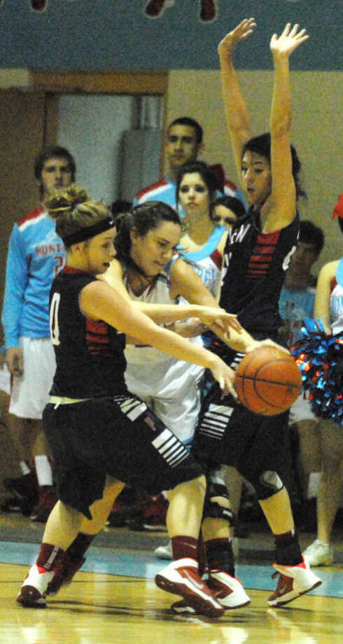 Plainview's Jaden Gonzales (left) and Shalee Bennett (right) sandwich a Monterey player during the second half of a District 4-4A girls basketball game in Lubbock Friday night. The play was indicative of the tough defense the Lady Bulldogs played in holding Monterey to just 13 points in the second half. Photo: Skip Leon/Plainview Herald