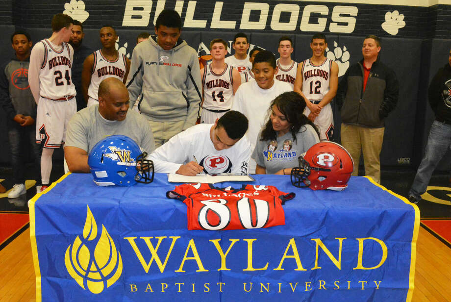 Plainview's Marc Wallace, seated center, signs a letter of intent Friday night to play football at Wayland Baptist University. Flanking Marc are his parents, Rodney, left, and Sarah, right. Standing and looking on are his brothers Christian, left, and Jordan. Photo: Skip Leon/Plainview Herald