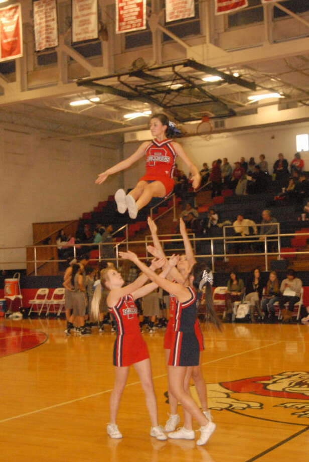 Doug McDonough/Plainview HeraldPlainview High Varsity Cheerleaders Kanzie Wieland (left), Jayci Gonzalez and Kimberly Gramaldo toss Lyndzee Chavez into the air during last Tuesday's Lubbock High-Lady Bulldogs game in Plainview. The Bulldogs and Lady Dogs will be back in the DogHouse tonight in a double-header against Hereford. The girls' game begins at 6 p.m. with the boys playing at 7:30 p.m.