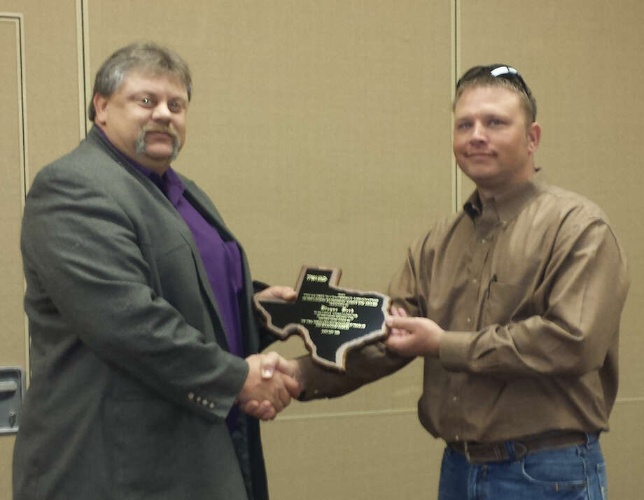 Blayne Reed (left), AgriLife Extension Integrated Pest Management specialist for Hale, Swisher and Floyd counties, receives the plaque as Outstanding IMP Agent from Chase Yankie of Hillsboro, president of the Texas Pest Management Association's annual meeting in San Angelo.