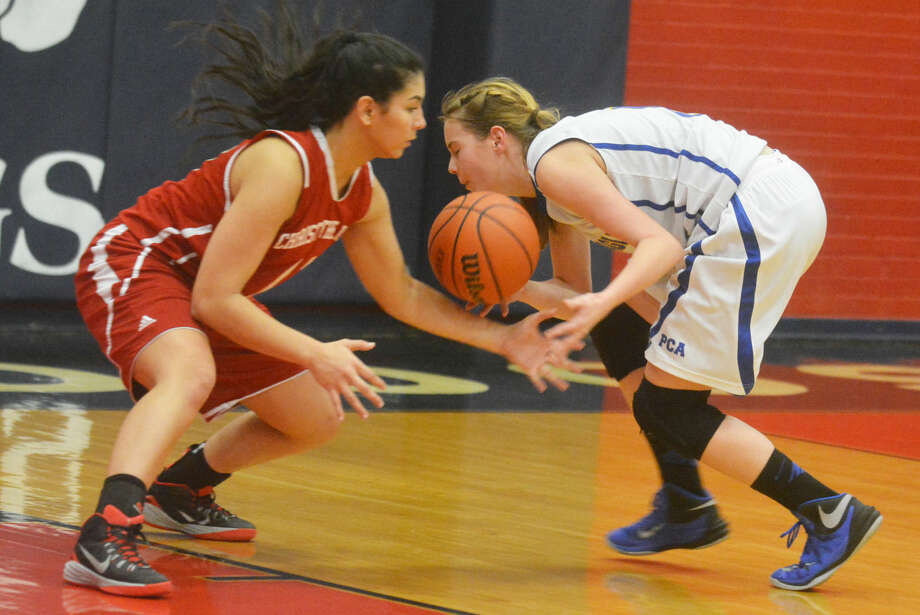 Plainview Christian Academy's Kylee Hill, right, tries to maintain control of the basketball as a Lubbock Christ the King defender tries to swat it away during a game at the Dog House in Plainview Friday night. The Lady Eagles' season came to an end with a 41-32 loss to CTK. Photo: Skip Leon/Plainview Herald