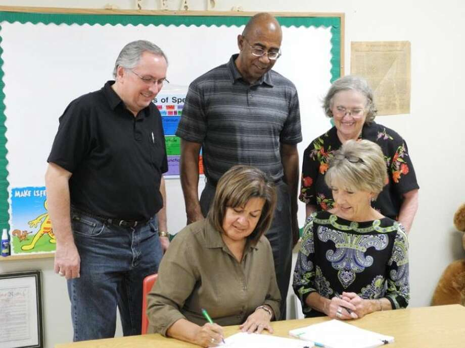 Lydia Castillo, director of Hale County Literacy Council, signs a contract that finalizes a federal grant for the Adult Basic Education/English as a Second Language programs in Plainview. Seated next to her is Brenda Cox, program and contract manager, South Plains Workforce Solutions. In back are Steve Long, incoming president, HCLC (left); Donald Hill, center director, South Plains Workforce Solutions; and Janice Payne, board treasurer, HCLC. Photo: Gail M. Williams/Plainview Herald