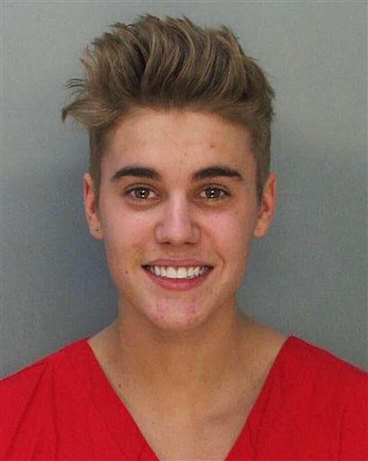 This police booking mug made available by the Miami Dade County Corrections Department shows pop star Justin Bieber, Thursday, Jan. 23, 2014. Bieber and singer Khalil were arrested for allegedly drag-racing on a Miami Beach Street. Police say Bieber has been charged with resisting arrest without violence in addition to drag racing and DUI. Police also say the singer told authorities he had consumed alcohol, smoked marijuana and taken prescription drugs. (AP Photo/Miami Dade County Jail) Photo: Uncredited / AP2014