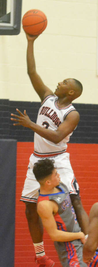Plainview's Ben McGee scores over an Abilene Cooper player during a game earlier this season. The Bulldogs finished off an unbeaten district campaign with a victory at Abilene Cooper Tuesday night. They will play Randall in the bi-district round of the playoffs Tuesday. Photo: Skip Leon/Plainview Herald