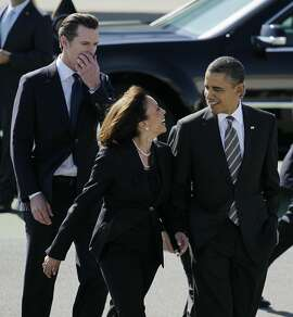 "In this Feb. 16, 2012 file photo President Barack Obama walks with California Attorney General Kamala Harris, center, and  California Lt. Gov. Gavin Newsom, after arriving at San Francisco International Airport in San Francisco. Obama praised California's attorney general for more than her smarts and toughness at a Democratic Party event Thursday, April 4, 2013. The president also commended Harris for being ""the best-looking attorney general"" during a Democratic fundraising lunch in the Silicon Valley. (AP Photo/Eric Risberg, File)"