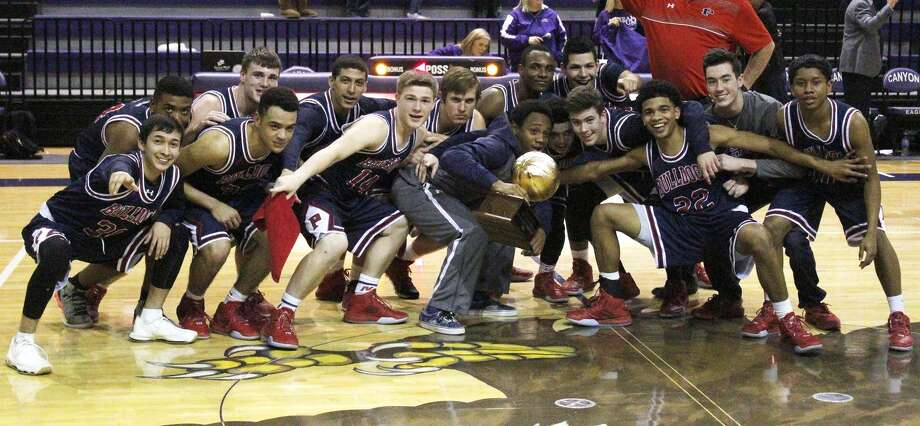 The Plainview Bulldog basketball team celebrates their Class 5A bi-district championship at Canyon High School Tuesday night. Plainview defeated Randall, 64-56, for their first postseason win since 2007. Photo: Photo Courtesy Of Tim Ritter/Canyon News