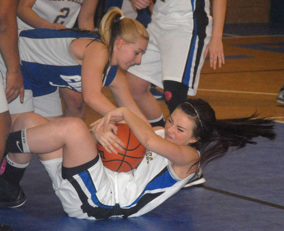 Plainview Christian Academy's Abbey Maresca cradles the ball as she falls to floor with an El Paso Jesus Chapel player trying to wrestler the basketball away from her during a TAPPS District 1-1A game at PCA Saturday morning. Photo: Skip Leon/Plainview Herald