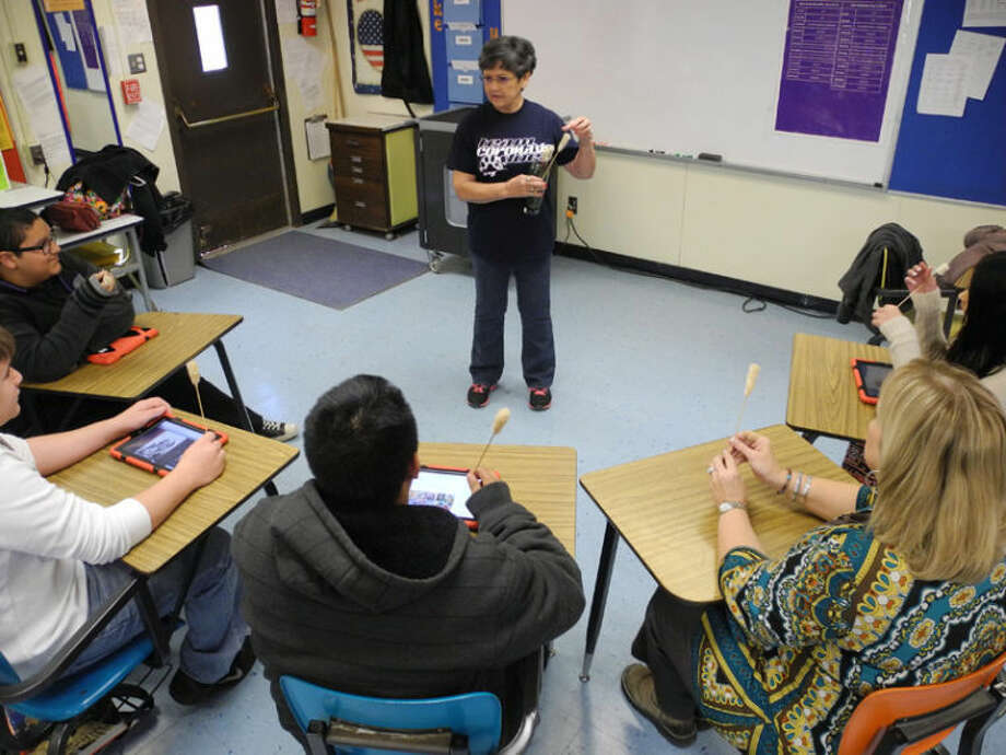 Anna Trusler, a descendant of Cherokees who survived the Trail of Tears, shows darts used by the tribe to hunt small game to students from Jennifer King's eighth grade history class. Photo: Gail M. Williams | Plainview Herald