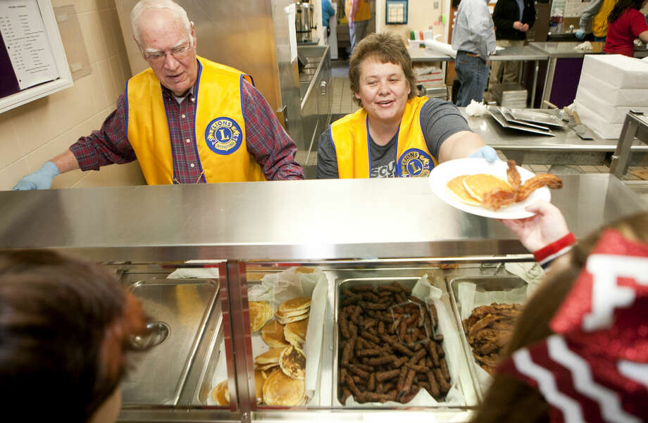 James Durbin/Midland Reporter-TelegramDon Eversole and Tammy Waller staff one of the serving lines Tuesday night during the 47th Annual Plainview Lions Club Pancake Supper. More than 800 people were feed during the event which is one of the organization's major fundraising events. Held in conjunction with the Plainview Bulldogs and Lady Bulldogs basketball double header against Lubbock Cooper, the dinner featured all-you-can eat pancakes, bacon and sausage at the Plainview High School cafeteria. Photo: James Durbin