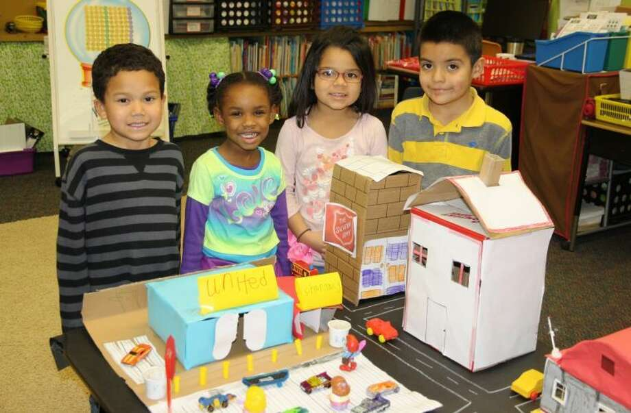 "Jan Seago/Plainview ISDThunderbird students Malakai Chambers (left), Raziya Sanders, Jazzalyn Ramirez and Uziel Esparza display a few of the replicas of local stores and businesses created by students from boxes as part of a social studies unit titled ""Our Community."" Kindergarten teachers are Heather Glenn, Mary Moralez, Christy Morgan and Jeremy Douglas."