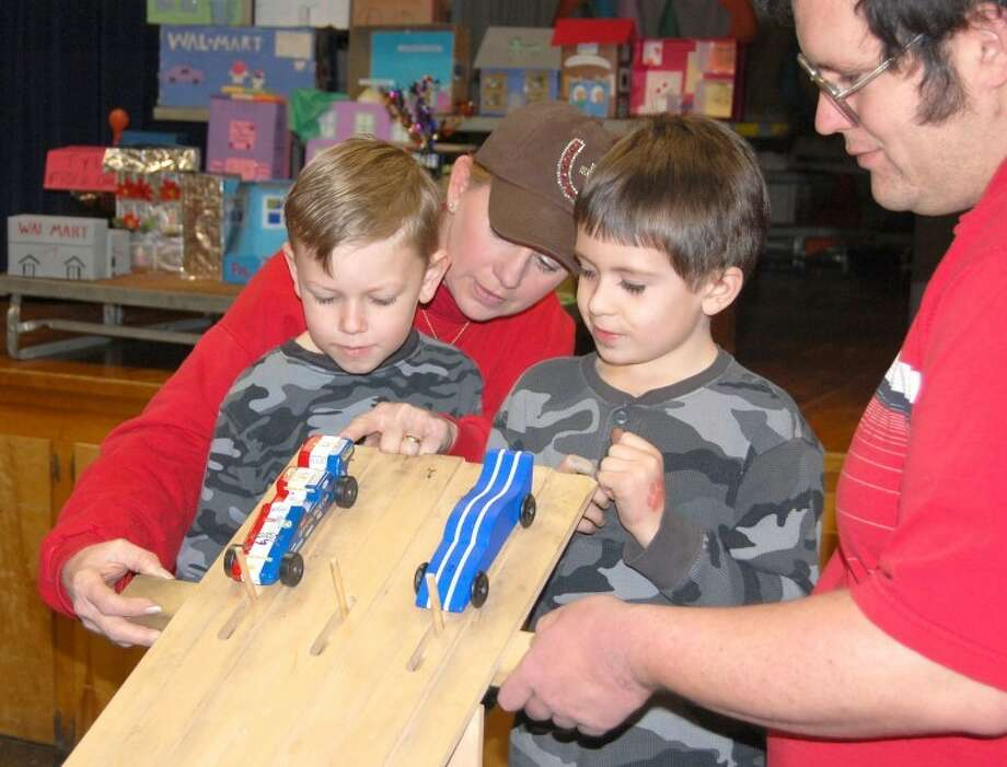 Herald File PhotoCub Scouts Eric Matthews (left) and Conner Kaylor get their Pinewood Derby cars ready to race with the help of leaders Lisa Wright and Michael Bechtold during a pack derby in 2011.