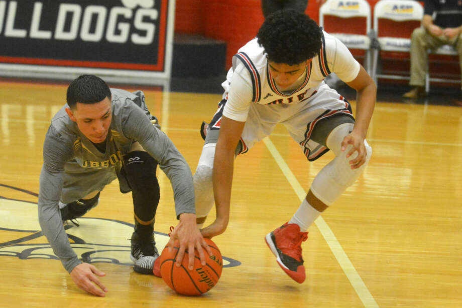 Plainview's Braxton Riddley (right) and Lubbock High's Jose Vallalobos (left) go after a loose ball during a District 4-5A basketball game at the Dog House Tuesday night. The Bulldogs won to set up a showdown with Abilene Cooper for the district title next Tuesday. Photo: Skip Leon/Plainview Herald