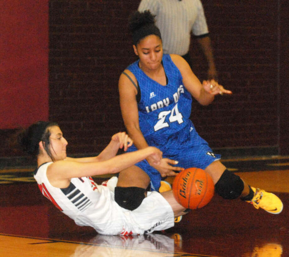 A Palo Duro player falls on top of Plainview's Shalee Bennett as the two battle for the ball in a bi-district playoff game Monday night. The Lady Bulldogs will take on El Paso Jefferson at 6 p.m. Thursday at Monahans in the area round. Photo: Skip Leon/Plainview Herald