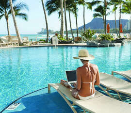 Hawaii, Oahu, Waikiki, Woman lounging at hotel poolside with laptop computer, Diamond Head in distance.
