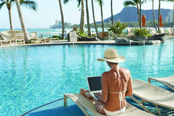 Hawaii, Oahu, Waikiki, Woman lounging at hotel poolside with laptop computer, Diamond Head in distance.