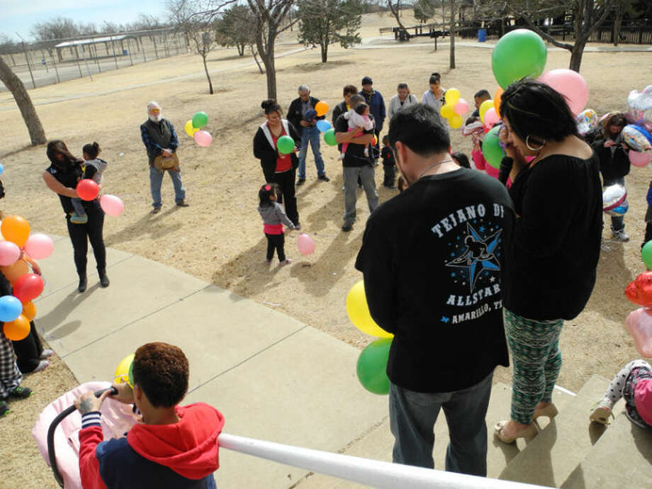 Joe Casas, Karaoke Joe of the Tejano All Starz DJs, stands next to Olivia Orona who leads a prayer for Brianna Lopez and other abused and neglected children at the balloon release in Kidsville on Valentine's Day. Photo: Gail M. Williams | Plainview Herald