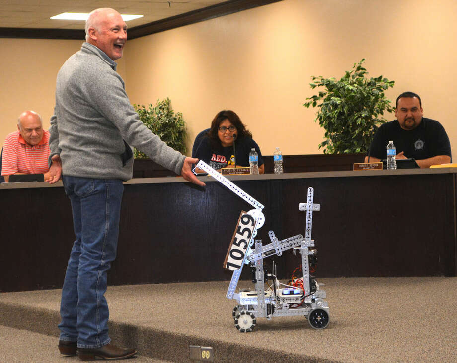 Doug McDonough/Plainview Herald Plainview ISD Superintendent Dr. Rocky Kirk chuckles has he shakes hands with RoboSpike during a demonstration of Plainview High robotics at Thursday's school board meeting. RoboSpike is the creation of Team 10559, one of three PHS groups that competed in the regional const at Frenship High School. The team finished second out of 36 teams.