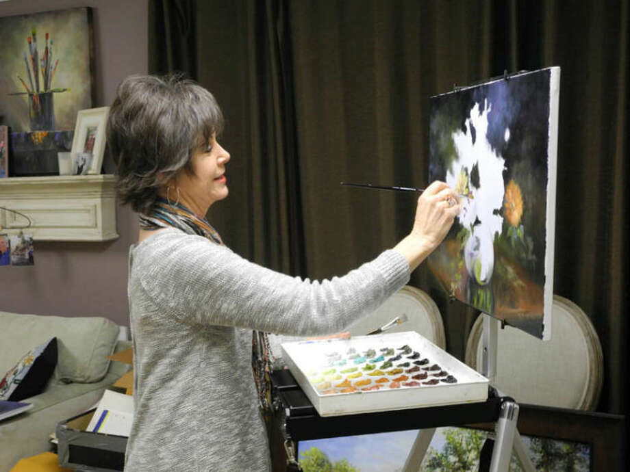 Sally Eaves blocks a still life with flowers in her basement studio using a palette she mixed herself. Photo: Gail M. Williams | Plainview Herald