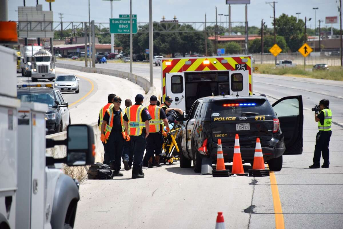 Emergency crews work to clear the scene of a three-car crash involving a San Antonio Police Department officer and cruiser, a CPS truck and a sedan on Interstate 35 near Southwest Military Drive on July 19, 2016.