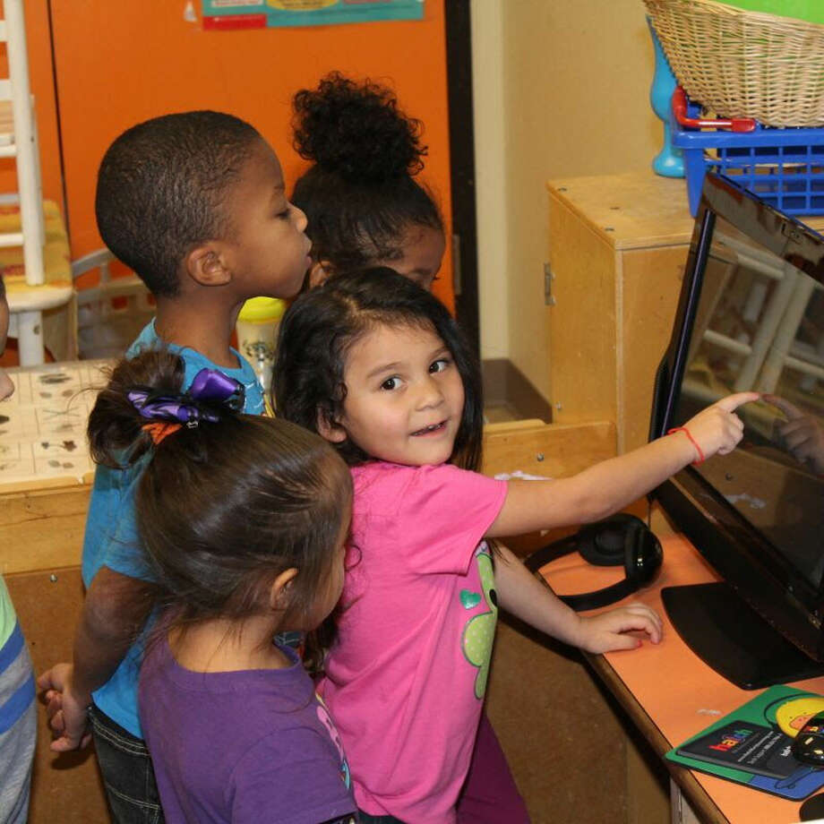 Arely Benavides, joined by Sky Thomas, Kollin Davis and D'Amberly Montelongo, point out a game on the new Hatch preschool computers recently purchased by the Wee Care Childcare Center. The new computers were a gift made in memory of the late Myrt Wilder. Photo: Courtesy Photo