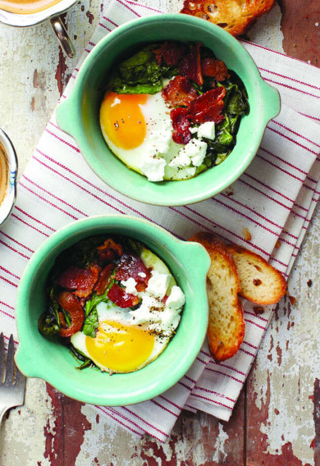 "What's for breakfast? Bacon and eggs make a delicious comeback, baked here with spinach and goat cheese. Credit: Sara Remington for ""Kitchen Confidence"" by Kelsey Nixon (Clarkson Potter, 2014)"