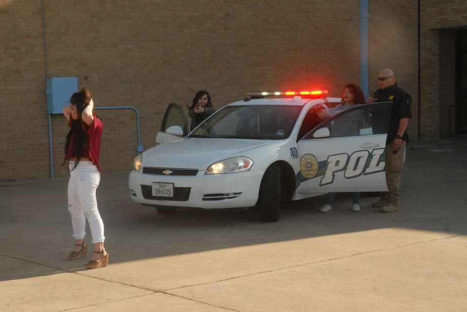 On Thursday, Plainview Police School Resource Officer Amos Rodriguez instructs students in a mock felony traffic stop at Plainview High School. The scenario is part of the school's Criminal Justice program which is taught by Rodriguez and other officers. Student Jailene Barrera acts the part of a suspect with her hands up as Kaitlyn Lopez and Angelicah Guevara act as officers during the stop. Photo: Homer Marquez/Plainview Herald