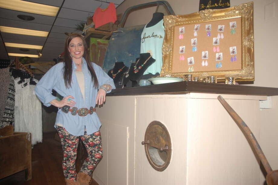 Andrea Glenn, proprietor of the Rusty Rose, stands next to her fashion inventory during the grand opening of new location, formerly the Plainview ISD tax office. Glenn's inventory is resting on a turn-of-the-century safe found in the historic building. Photo: Homer Marquez/Plainview Herald